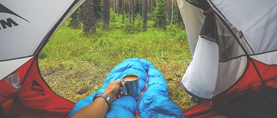 A man drinking coffee from a mug in a rented sleeping bag inside a hiking tent