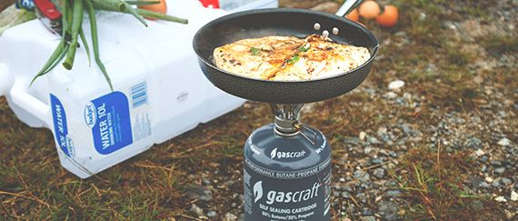 Hiking and having a delicious omlette on a pan on a portable camping gas stove